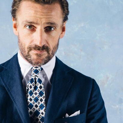 veste bleu chemise blanche cravate blanche et bleue